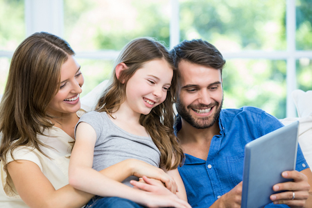 Jeune famille regardant tablette à la maison