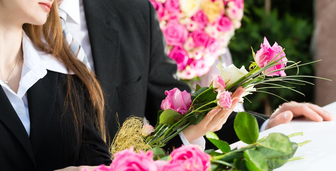 Jeune femme et jeune homme en deuil à des funérailles avec des roses en mains